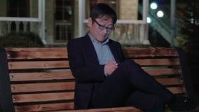 De Aziatische mens in een kostuum schrijft een tekstbericht en glimlacht De avond stock footage