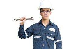 De Aziatische mens, de Ingenieur of de Technicus in witte helm, glazen en blauw werkend overhemd passen holdingsmoersleutel aan,  royalty-vrije stock afbeeldingen