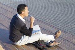 De Aziatische mens leest zorgvuldig en schrijft royalty-vrije stock foto