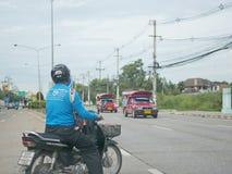 De Aziatische mens op een motor neemt een haastig besluit om een u-Draai in verkeer te maken Royalty-vrije Stock Afbeelding