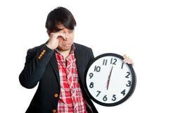 De Aziatische mens slaperig in de ochtend houdt een klok stock afbeeldingen