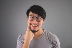 De Aziatische mens vervalst zijn glimlach Royalty-vrije Stock Foto's