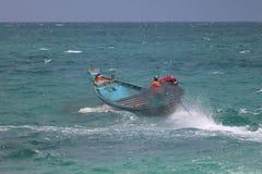 De Aziatische mensen drijven de lange staartboot in het overzees, terwijl een sterke wind en de golven royalty-vrije stock foto