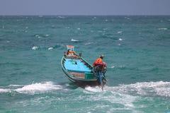 De Aziatische mensen drijven de lange staartboot in het overzees, terwijl een sterke wind en de golven stock foto's