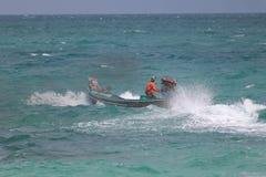 De Aziatische mensen drijven de lange staartboot in het overzees, terwijl een sterke wind en de golven stock foto