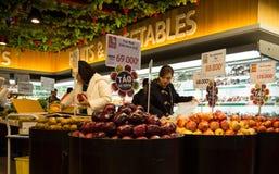 De Aziatische mensen gaan winkelend bij een supermarkt en kiezend vers fruit Royalty-vrije Stock Afbeelding