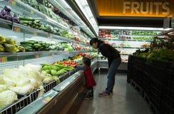 De Aziatische mensen gaan winkelend bij een supermarkt en kiezend vers fruit Royalty-vrije Stock Foto's