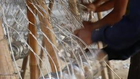 De Aziatische mensen` s handen breien metaalnetwerk voor de omheining stock footage