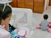 De Aziatische moeder die het bezige vouwen kleedt zich terwijl tegelijkertijd het behandelen van haar twee dochters zijn royalty-vrije stock foto