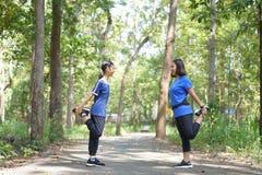 De Aziatische moeder en de dochter warmen alvorens bij het park te lopen op royalty-vrije stock afbeeldingen
