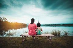 De Aziatische moeder en haar dochter zitten op de banken van een rustige avondlagune stock fotografie