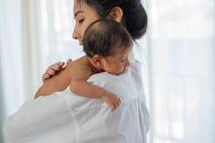 De Aziatische moeder met witte overhemdsplaats op de schouder van weinig pasgeboren baby nadat geef melk en baby kijkt slaperig stock fotografie