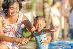 De Aziatische moeder moedigt peuter aan die pret hebben bij zwembad Stock Fotografie