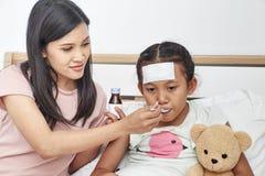 De Aziatische moeder neemt zorg zieke dochter op bed Stock Afbeelding