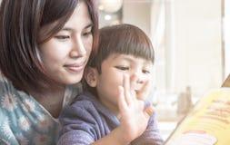 De Aziatische Moeder onderwijst haar zoon om een boek te lezen stock afbeeldingen