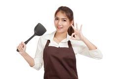 De Aziatische mooie meisjeskok toont o.k. met spade van pan Stock Foto's