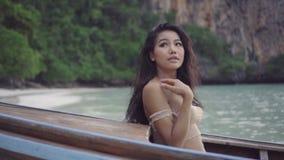 De Aziatische mooie sensuele vrouw haakt binnen bikini op de boot Video van sexy meisjeszitting op de boot en het kijken omhoog a stock videobeelden