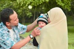 De Aziatische moslimhijabimoeder en de vader lopen door het park met zoon in wandelwagen terwijl zijn mamma die haar todler behan stock afbeelding