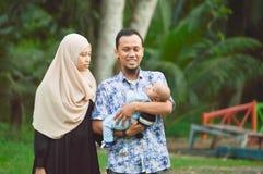 De Aziatische moslimhijabimoeder en de vader lopen door het park met zoon in wandelwagen terwijl zijn mamma die haar todler behan stock afbeeldingen