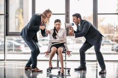 De Aziatische onderneemster bond met kabel op stoel terwijl zakenlieden die op haar met megafoon gillen stock foto's