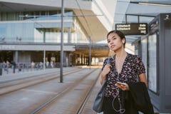 De Aziatische onderneemster die op een tram tijdens haar ochtend wachten zet om royalty-vrije stock foto's