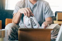 De Aziatische ondernemerstiener draagt babyschoenen en wordt gezet in een klant van de kartondoos om het product thuis te leveren stock afbeeldingen