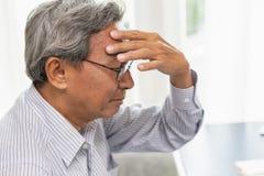 De Aziatische oudere hoofdpijnpijn lijdt aan spanning royalty-vrije stock afbeelding