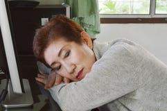 De Aziatische oudere vrouw neemt een dutje op het bureau voor personal computer Royalty-vrije Stock Fotografie