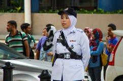 De Aziatische politievrouw bevindt zich langs de weg in wit eenvormig, een GLB en hijab stock afbeeldingen