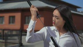 De Aziatische schoonheid trekt schitterend zwaard uit zijn schede en bekijkt adoringly het stock video
