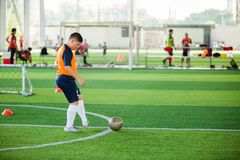 De Aziatische snelheid van de jongensvoetballer loopt om bal aan doel op kunstmatig gras te schieten royalty-vrije stock afbeelding