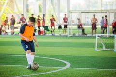 De Aziatische snelheid van de jongensvoetballer loopt om bal aan doel op kunstmatig gras te schieten stock foto