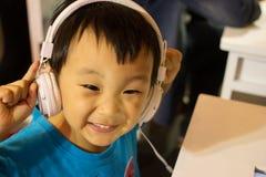 De Aziatische spelen van de computerinternet van het jong geitjespel en slijtagehoofdtelefoon Stock Foto