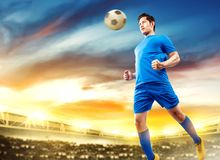 De Aziatische sprong van de voetbalstermens in de lucht en de rubriek de bal stock foto