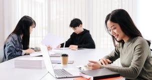 De Aziatische de Studentesglimlach en lezing boeken en gebruikend notitieboekje voor hulp om idee?n in het werk en het project te stock fotografie
