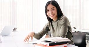 De Aziatische de Studentesglimlach en lezing boeken en gebruikend notitieboekje voor hulp om idee?n in het werk en het project te royalty-vrije stock afbeeldingen