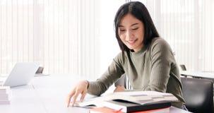 De Aziatische de Studentesglimlach en lezing boeken en gebruikend notitieboekje voor hulp om idee?n in het werk en het project te royalty-vrije stock afbeelding