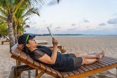 De Aziatische tablet van het toeristengebruik om Internet op het strand te surfen stock afbeelding