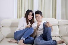 De Aziatische televisie van paarhorloges samen thuis royalty-vrije stock afbeeldingen