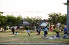 De Aziatische Thaise familie ontspant spel met picknick en mensen die oefening aanstoten bij speelplaats op yard in openbaar tuin royalty-vrije stock afbeeldingen