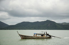 De Aziatische Thaise mensen die houten motorboot op het overzees drijven voor verzenden Stock Foto's
