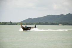 De Aziatische Thaise mensen die houten motorboot op het overzees drijven voor verzenden Stock Foto