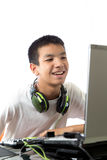 De Aziatische tiener die computer met behulp van met smily ziet onder ogen Stock Foto