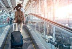 De Aziatische tiener gebruikt een smartphone om vlucht bij de internationale luchthaven te controleren Stock Foto