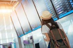 De Aziatische tiener gebruikt een smartphone om vlucht bij de internationale luchthaven te controleren Stock Afbeeldingen