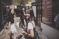 De Aziatische tiener het glimlachen emotie die van het gezichtsgeluk in citylifestraat lopen stock foto's