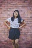 De Aziatische tiener stelt als mannequin tegen rode bakstenen muur stock afbeelding
