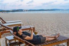 De Aziatische toerist ontspant en gebruikt tablet op strand stock afbeeldingen