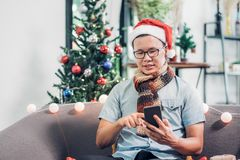 De Aziatische van de santahoed van de mensenslijtage van de het gebruiks mobiele vraag vrienden en de zitting  royalty-vrije stock afbeelding