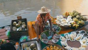 De Aziatische verkoper op kleine boot met vruchten en groenten verkoopt de goederen Pattaya het drijven markt stock video